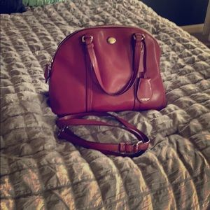 A wine colored coach mid-sized purse with strap.